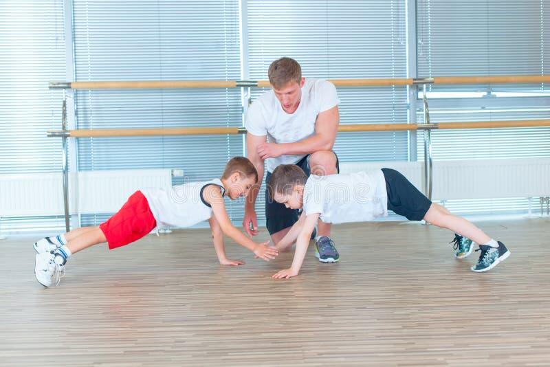做在健身房的小组孩子孩子体操与老师 健身房的愉快的运动的孩子 酒吧锻炼 板条 免版税库存图片