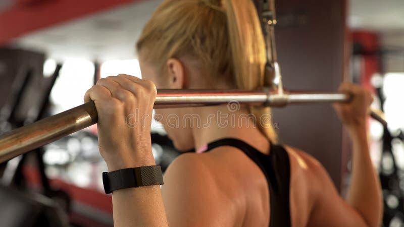 做在健身房的少妇后方折叠式的,解决有梦想适合的身体 免版税库存照片