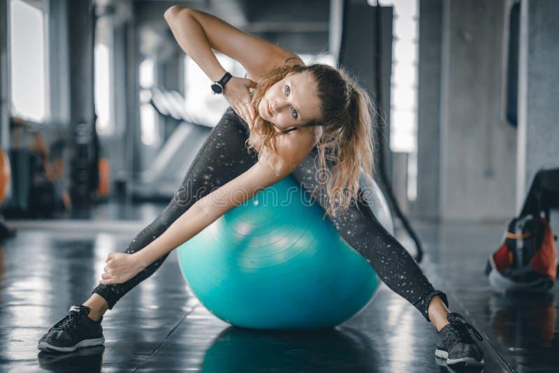 做在健身房的年轻有吸引力的妇女健身锻炼锻炼 舒展肌肉和放松的妇女 库存照片