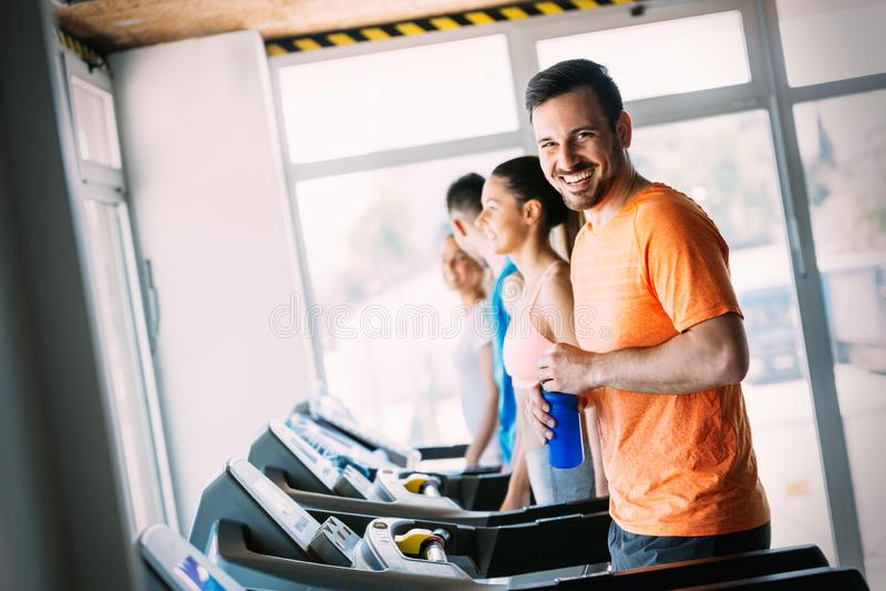 做在健身房的年轻英俊的人心脏训练 库存照片