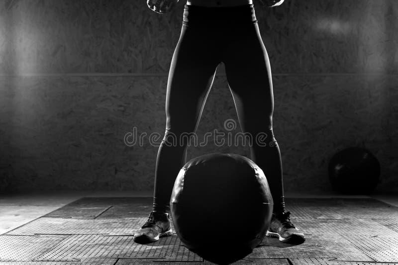 做在健身房的年轻运动的妇女力量锻炼 图库摄影