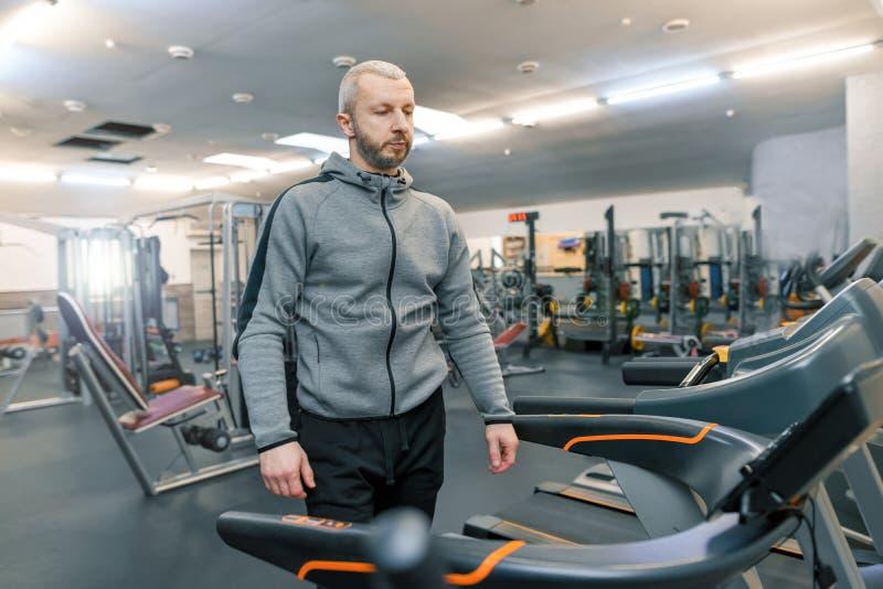 做在健身房的成人英俊的有胡子的人锻炼 体育修复,年龄,健康生活方式概念 免版税库存图片