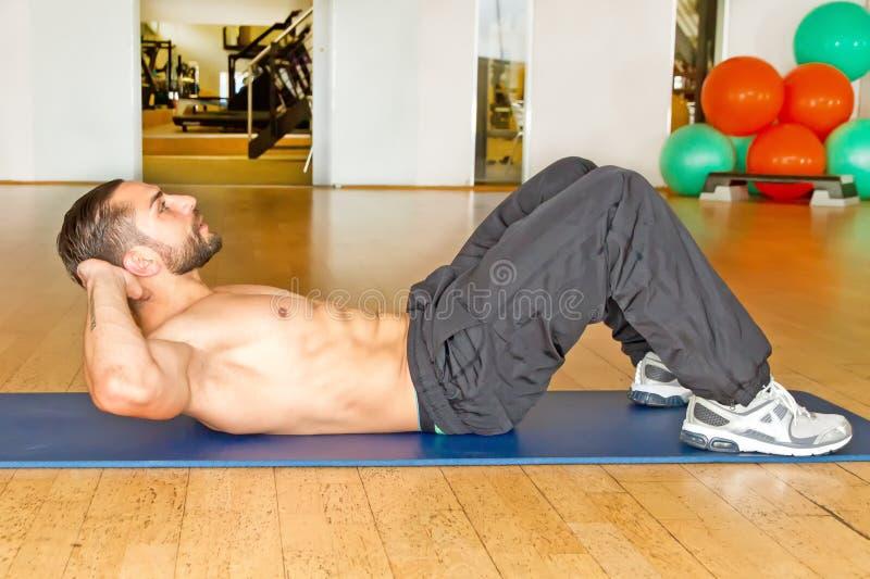 做在健身房的肌肉人胃肠咬嚼 免版税图库摄影