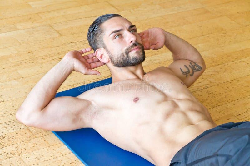 做在健身房的肌肉人胃肠咬嚼 图库摄影