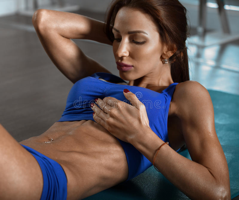 做在健身房的肌肉妇女吸收咬嚼 库存图片