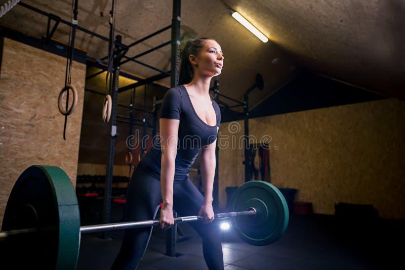 做在健身房的肌肉年轻健身妇女重的deadlift锻炼 库存照片