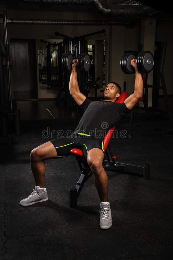 做在健身房的年轻人卧推锻炼 图库摄影