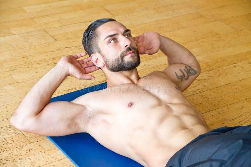 做在健身房的年轻人胃肠咬嚼 库存图片