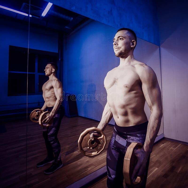 做在健身房赤裸躯干的肌肉爱好健美者人锻炼 被定调子的图象 免版税库存图片