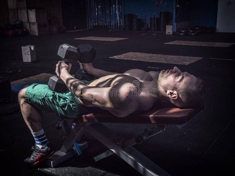 做在健身房长凳的英俊的年轻人吸收锻炼 免版税库存图片