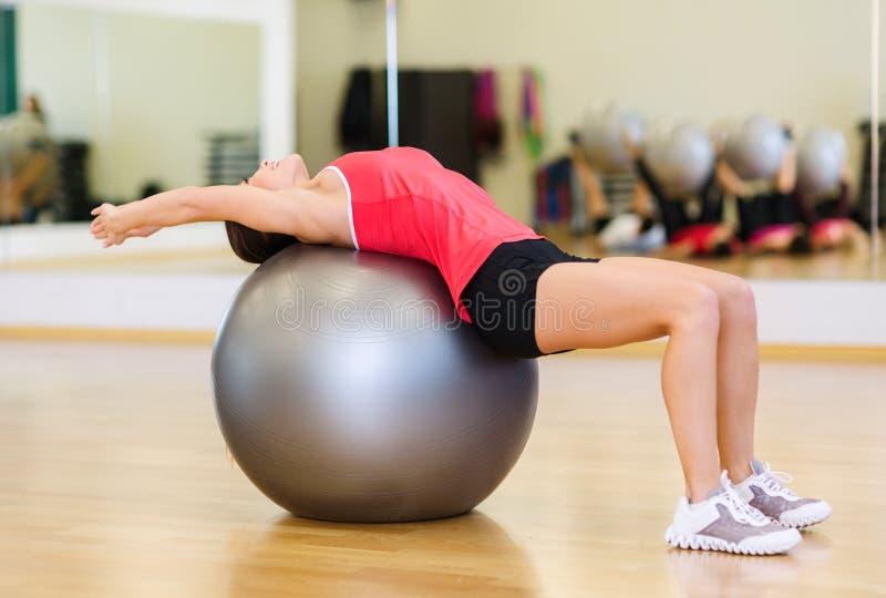 做在健身球的少妇锻炼 库存照片