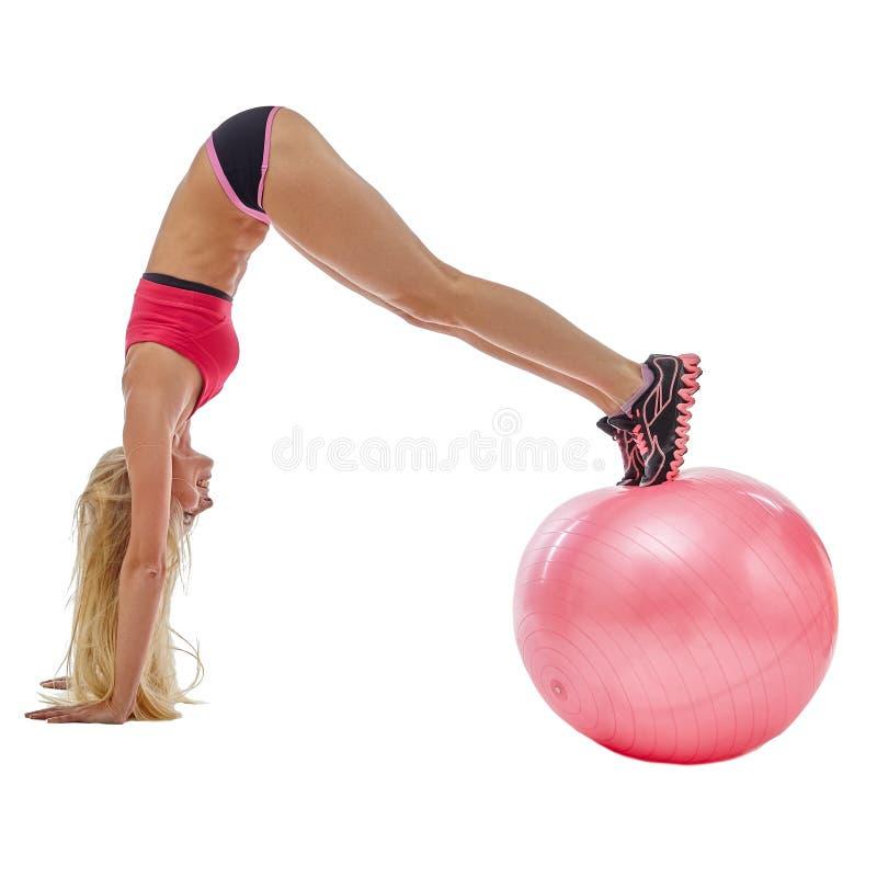 做在健身球的精力充沛的女孩手倒立 免版税图库摄影