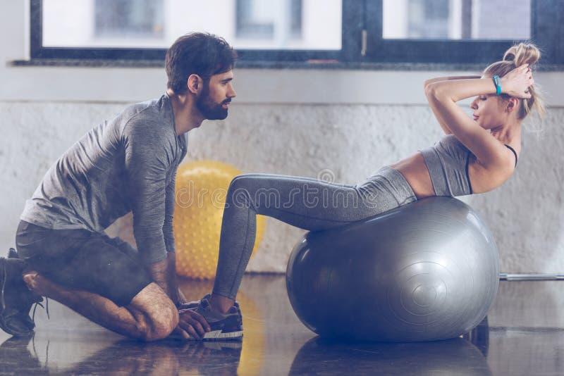 做在健身球的运动年轻女运动员吸收在健身房 免版税库存图片
