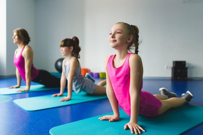 做在健身类的女孩和辅导员或者母亲体操锻炼 库存图片