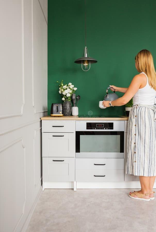 做在典雅的厨房内部的年轻白肤金发的妇女茶 库存图片