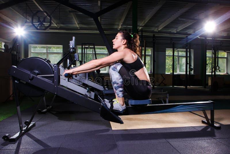做在划船器的年轻坚强的女孩一锻炼 对训练心脏胳膊,后面 体育概念 免版税库存图片