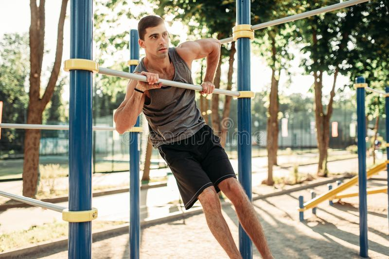做在单杠的人锻炼室外 免版税库存照片