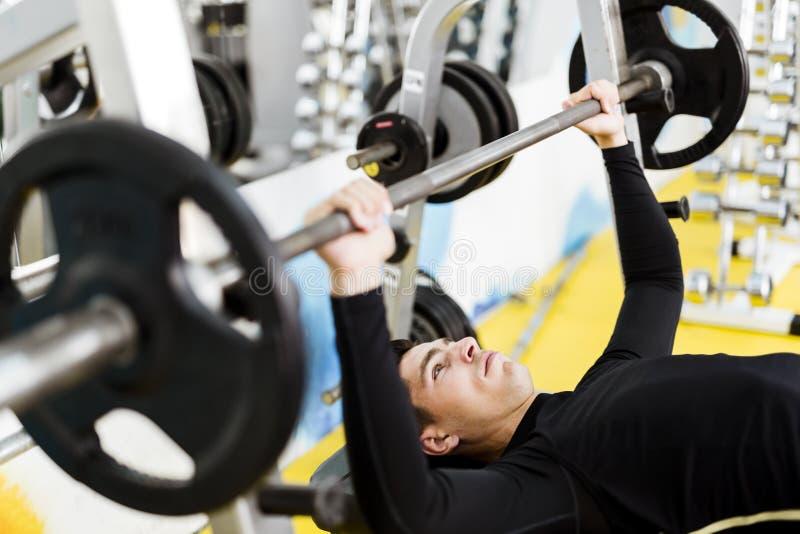做在卧推的年轻英俊的人特写镜头锻炼 免版税库存图片