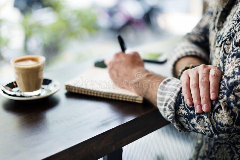 做在咖啡店的作者笔记 免版税图库摄影