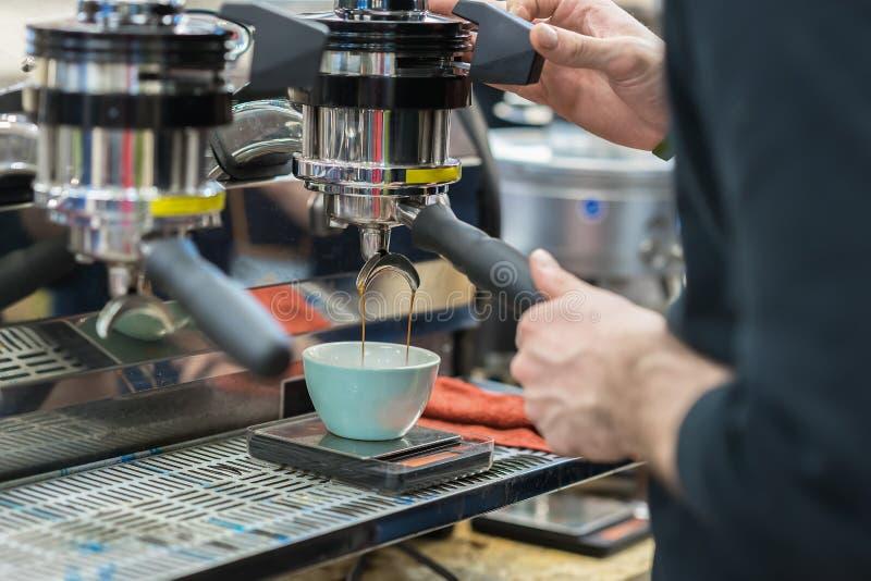 做在咖啡机器的咖啡 ` s手准备咖啡的人,新鲜的浓咖啡涌入瓷杯子 为服务和 库存图片