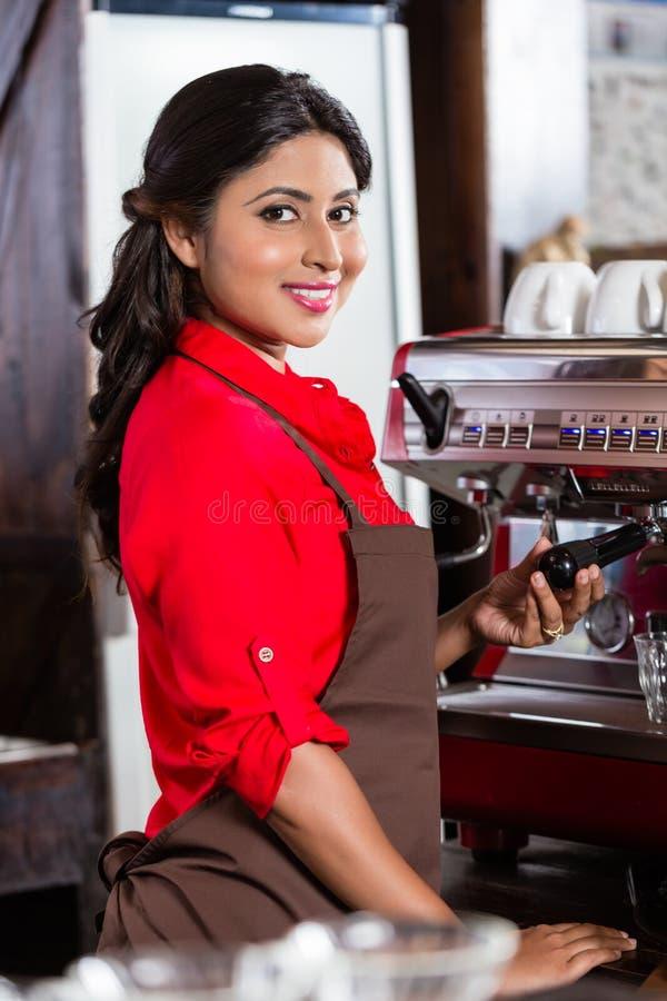 做在咖啡馆的Barista妇女咖啡与机器 免版税库存照片
