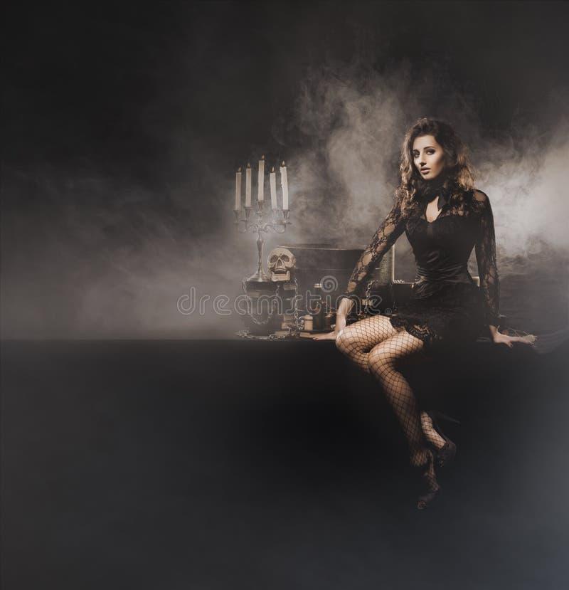 做在土牢的年轻性感的巫婆巫术 免版税库存图片