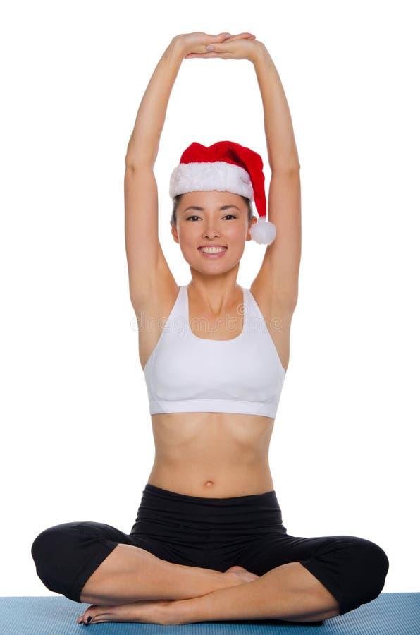 做在圣诞老人盖帽的亚裔女孩瑜伽  免版税库存照片