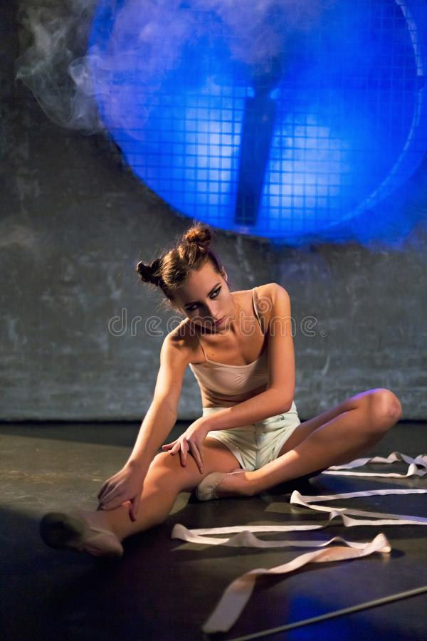 做在地板上的年轻美丽的体操运动员妇女伸展运动在健身房 库存图片