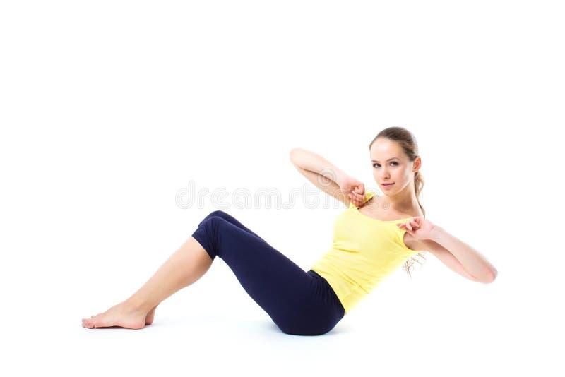 做在地板上的美丽的运动的妇女锻炼被隔绝 免版税库存图片
