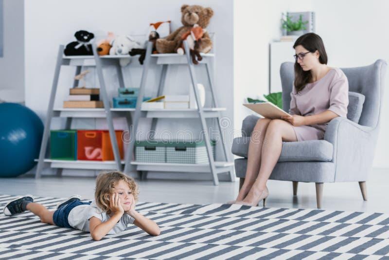 做在地板上说谎在心理学办公室的诊断的一位专业治疗师一个孤独孩子 图库摄影