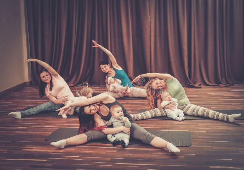 年轻做在地毯的母亲和他们的婴孩瑜伽锻炼在健身演播室 库存照片
