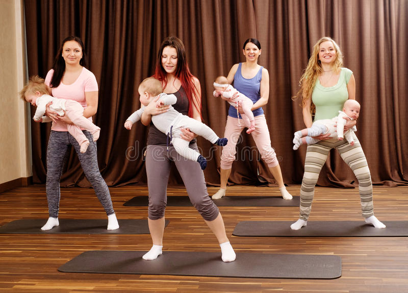 年轻做在地毯的母亲和他们的婴孩瑜伽锻炼在健身演播室 库存图片