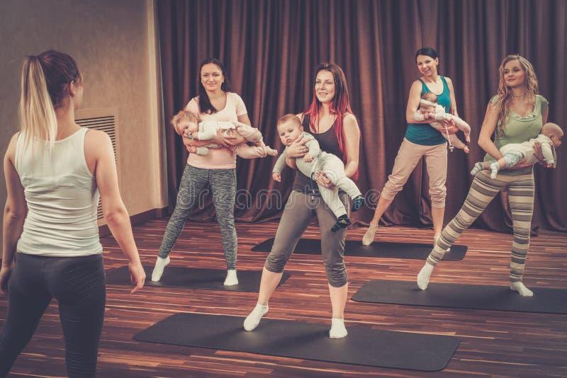 年轻做在地毯的母亲和他们的婴孩瑜伽锻炼在健身演播室 免版税库存照片