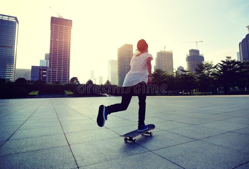 做在城市的溜冰板者踩滑板的把戏ollie 图库摄影