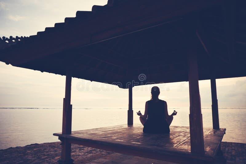 做在太阳风雨棚的妇女剪影瑜伽实践在海洋附近 免版税库存照片