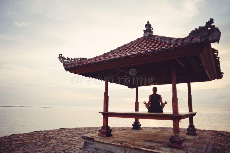 做在太阳风雨棚的少妇瑜伽实践在海洋附近 免版税库存图片
