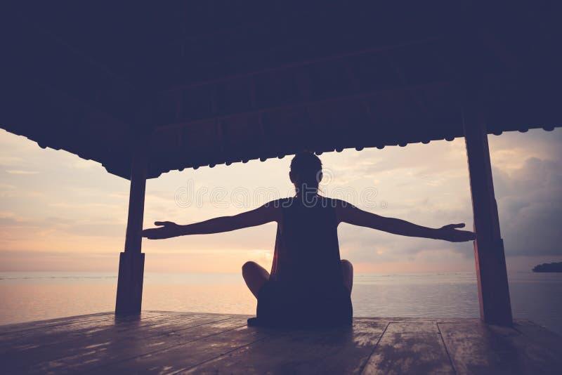 做在太阳风雨棚的愉快的妇女剪影健身实践在海洋附近 库存照片