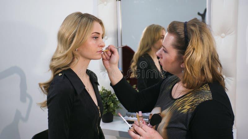 做在她的嘴唇的美丽的白肤金发的妇女特写镜头画象构成 免版税库存照片