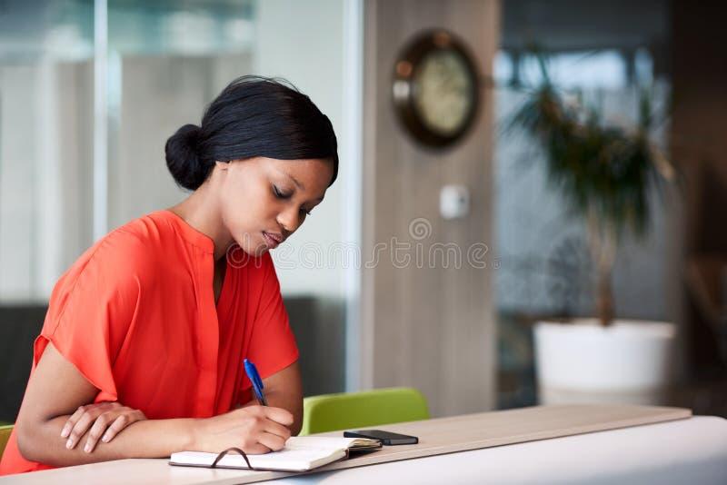 做在她的笔记本的黑人学生笔记在家坐 图库摄影