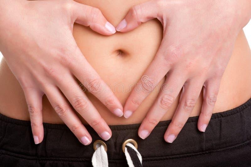 做在她的肚子的妇女心脏标志 库存照片