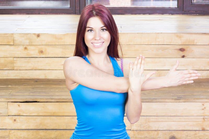 做在她的胳膊的愉快的妇女锻炼 球概念健身pilates放松 图库摄影