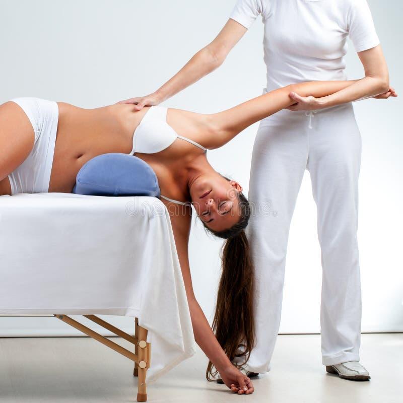做在妇女的治疗师肩膀按摩 图库摄影