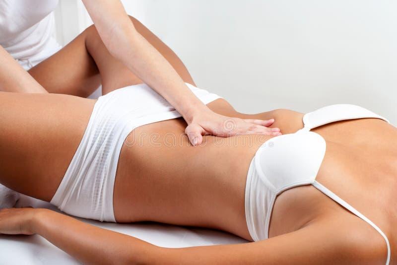 做在妇女的治疗师胃肠按摩 免版税库存照片