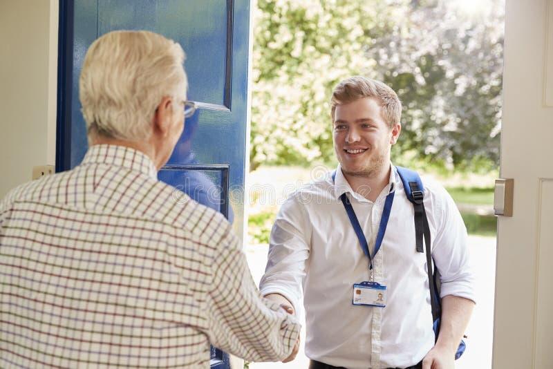 做在家参观的老人问候男性关心工作者 免版税图库摄影
