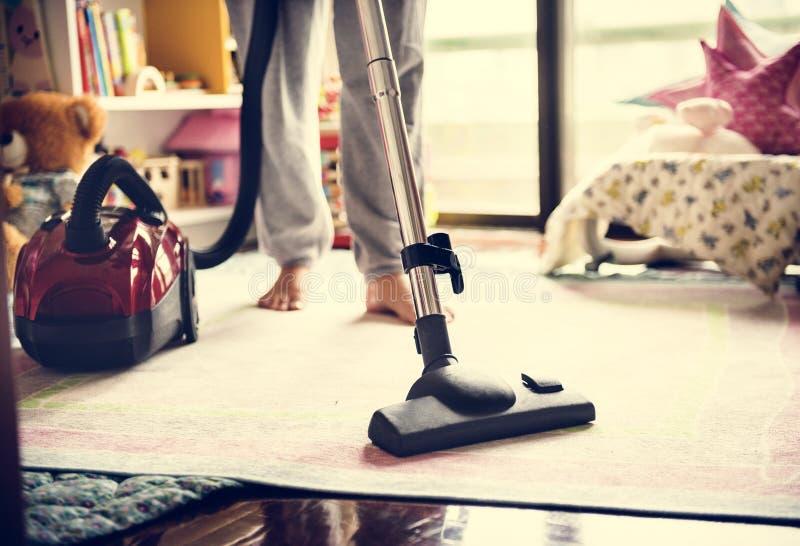 做在家清洗与吸尘器的妇女 库存照片
