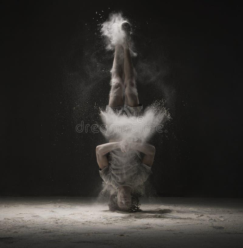 做在尘云视图的年轻舞蹈家一headstand 库存图片