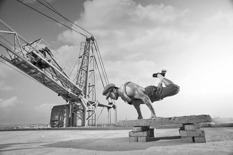 做在屋顶o的运动强的肌肉建造者手倒立 图库摄影