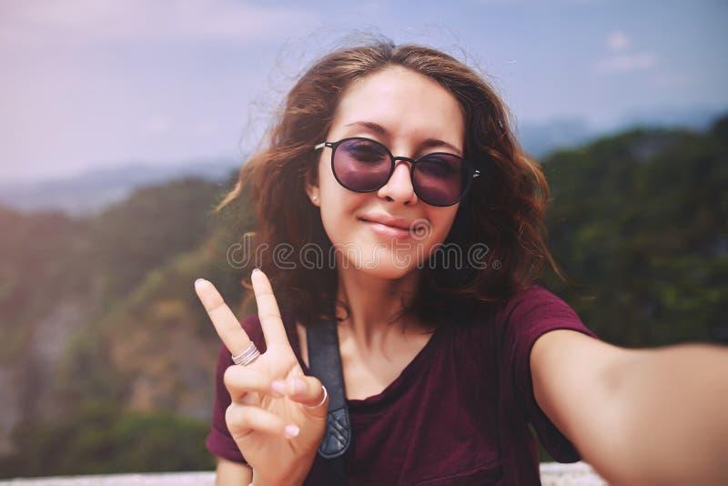 做在山的一微笑的少女的画象selfie照片 图库摄影