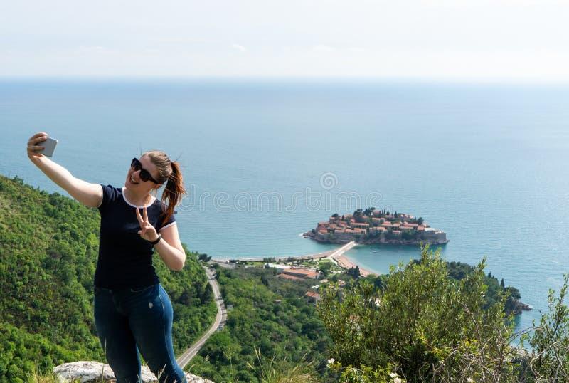 做在山的一selfie和亚得里亚海的年轻白女孩在背景和圣斯特凡岛中 有智能手机的妇女 免版税库存照片
