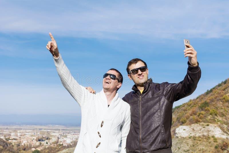 做在山的两个微笑的年轻人画象selfi 库存图片